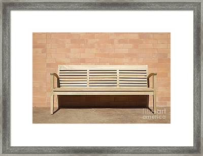 Wooden Bench Set Against Brick Wall Framed Print by Jeremy Woodhouse