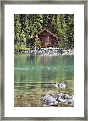 Wooden Cabin Along A Lake Shore Framed Print by Michael Interisano