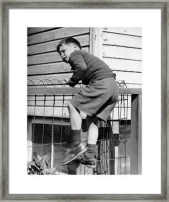 Young Boy Climbing Fence Framed Print by George Marks