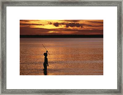 Young Boy Spear Fishing At Sunset Framed Print by Gerry Ellis