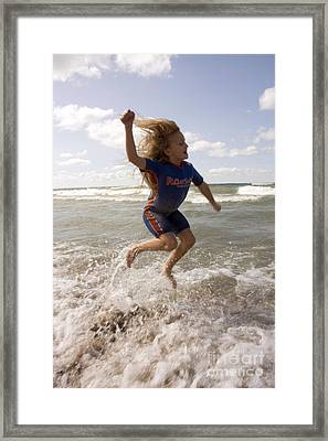 Young Girl Jumping Above Surf Framed Print by Christopher Purcell