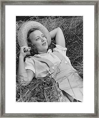 Young Woman Laying In Hay Thinking Framed Print by George Marks