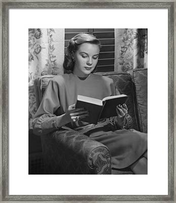 Young Woman Sitting On Sofa, Reading Book, (b&w) Framed Print by George Marks