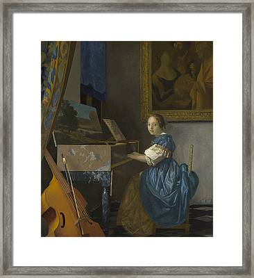 A Young Woman Seated At A Virginal Framed Print by Johannes Vermeer