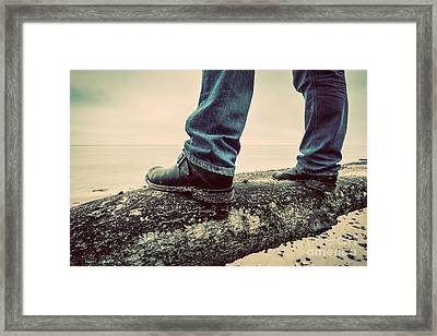 Man In Jeans And Elegant Shoes Standing On Fallen Tree On Wild Beach Looking At Sea Framed Print