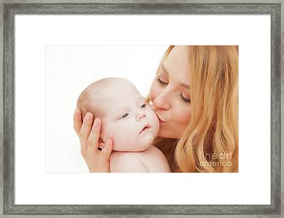 Mother Holding And Kissing Her Newborn Baby. Motherhood Framed Print