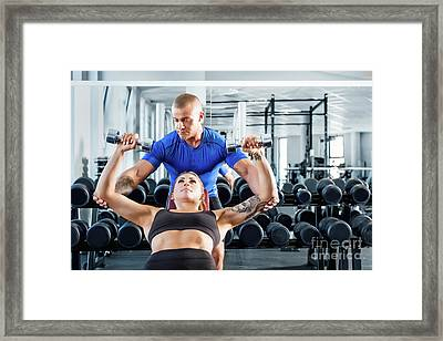 Personal Trainer Assisting While Exercises At The Gym. Framed Print
