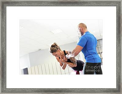 Personal Trainer Working With A Client At The Gym. Framed Print