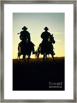 Silhouetted Cowboys Framed Print by Inga Spence