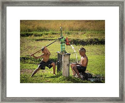 Framed Print featuring the photograph Two Young Boy Rocking Groundwater Bathe In The Hot Days. by Tosporn Preede