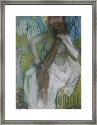 Woman Combing Her Hair Framed Print by Edgar Degas