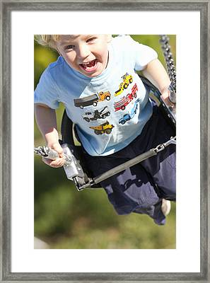 Young Boy Smiling Swinging In A Swing Framed Print by Robert Postma