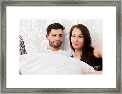 Young Couple Snuggling In Bed Framed Print