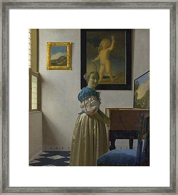 A Young Woman Standing At A Virginal Framed Print by Johannes Vermeer