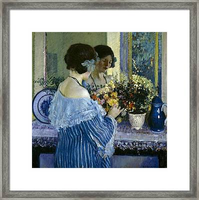 Girl In Blue Arranging Flowers Framed Print by Frederick Carl Frieseke