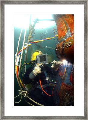 U.s. Navy Diver Welds A Repair Patch Framed Print by Stocktrek Images