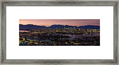 Aerial View Of A City Lit Up At Dusk Framed Print