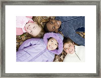 Smiling Children Lying On Autumn Leaves Framed Print by Ian Boddy