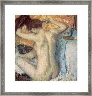 Woman Combing Her Hair Framed Print by Edgar Degas
