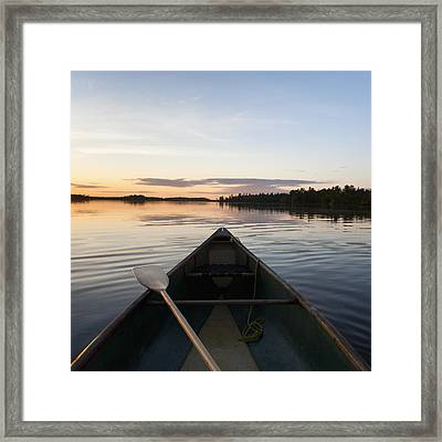 A Boat And Paddle On A Tranquil Lake Framed Print