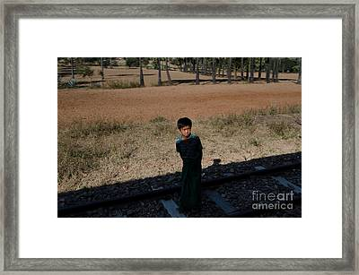 Framed Print featuring the photograph A Boy In Burma Looks Towards A Train From The Shadows by Jason Rosette