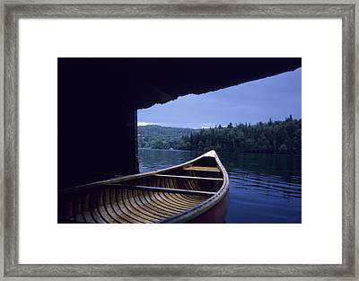 A Canoe Sticks Out Of A Boathouse On An Framed Print by Taylor S. Kennedy