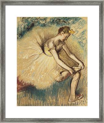 A Dancer Putting On Her Shoe Framed Print by Edgar Degas