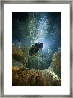 A Diver Ascends A Deep Shaft In Dans Framed Print by Wes C. Skiles