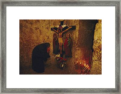 A Greek Pilgrim Prays In The Grotto Framed Print by Annie Griffiths