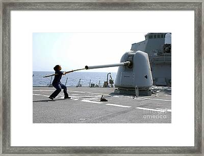 A Gunners Mate Cleans The Barrel Framed Print by Stocktrek Images