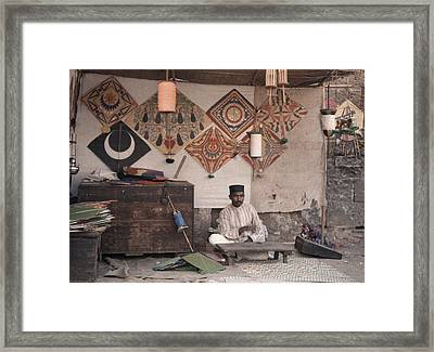 A Kite Merchant Sits In His Store Framed Print by Gervais Courtellemont