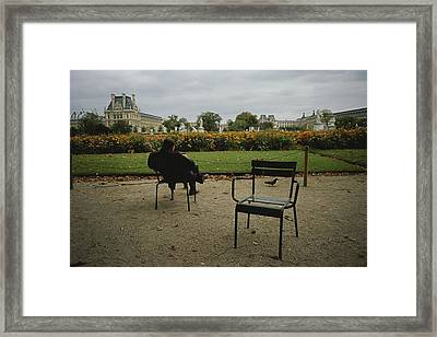 A Man Reads In The Tuileries Gardens Framed Print by Raul Touzon