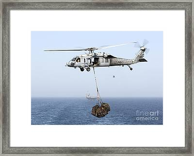 A Mh-60 Helicopter Transfers Cargo Framed Print by Gert Kromhout