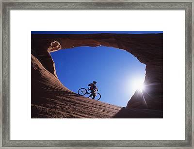A Mountain Biker Stands Under An Arch Framed Print by Bill Hatcher