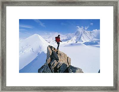 A Mountain Climber Summits Mount Framed Print by Gordon Wiltsie