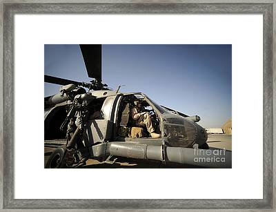 A Pilot Sits In The Cockpit Of A Hh-60g Framed Print by Stocktrek Images
