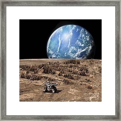 A Rover Explores A Rocky, Barren Moon Framed Print by Marc Ward