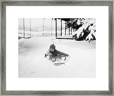 A Small Girl On A Sled Framed Print