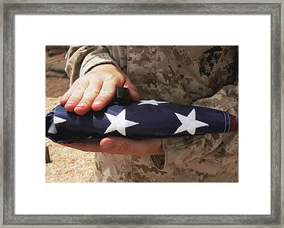 A Soldier Holds The United States Flag Framed Print by Stocktrek Images