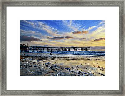 A Surfer Heads Home Under A Cloudy Sunset At Crystal Pier Framed Print