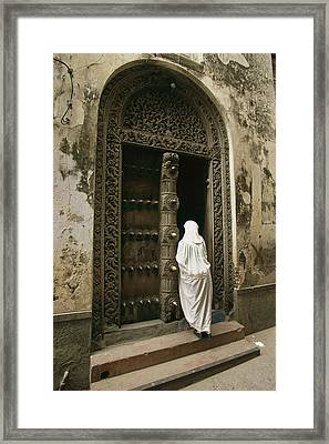 A Swahili Woman Enters A Building Framed Print by Michael S. Lewis