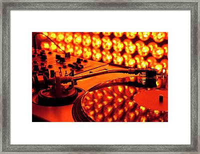 A Turntable And Sound Mixer Illuminated By Lighting Equipment Framed Print