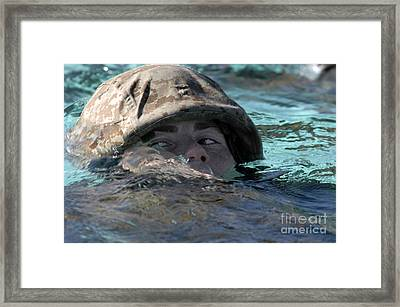 A U.s. Marine Swims Across A Training Framed Print by Stocktrek Images