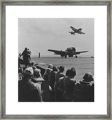 A Us Navy Hellcat Fighter Aircraft Landing On The Deck Of A Carrier Framed Print by American School