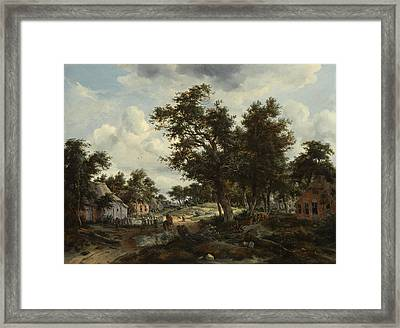 A Wooded Landscape With Travelers On A Path Through A Hamlet Framed Print by Meindert Hobbema