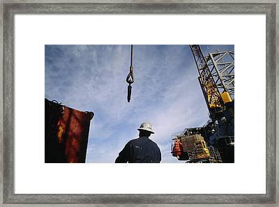 A Worker Uses A Crane And Hoist To Lift Framed Print by Justin Guariglia