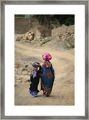 A Yemeni Woman And Child Carrying Framed Print by Michael Melford