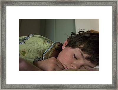 A Young Boy Sleeps In Green Pajamas Framed Print by Joel Sartore
