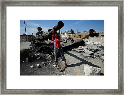 A Young Syrian Boy Plays On The Turret Framed Print by Andrew Chittock