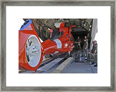 An Aircrew Loads A Coast Guard Hh-65 Framed Print by Stocktrek Images